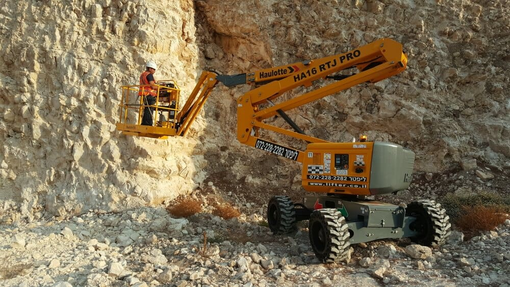 במת זרוע דיזל בצבע צהוב, עבודת חוץ ליד סלעים