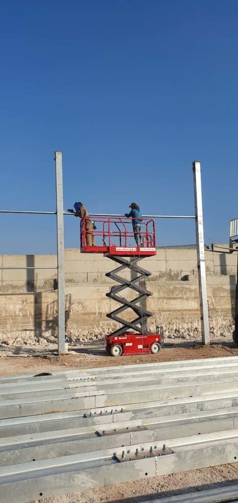 במת מספריים חשמלית 8 מטר בצבע אדום, עבודת חוץ באתר בניה