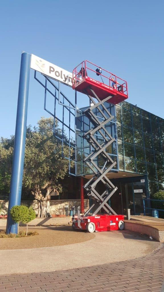 במת מספריים 10 מטר בצבע אדום, עבודת חוץ על שלט בניין