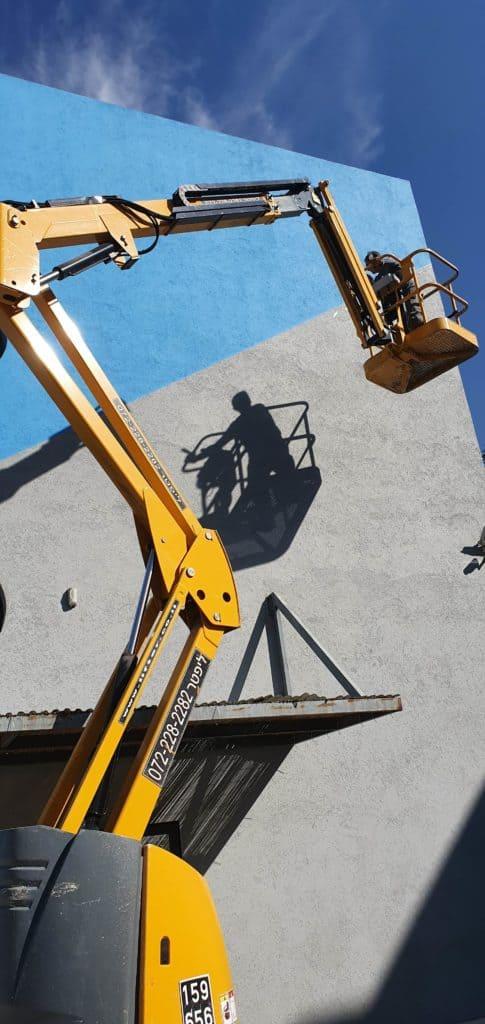 במת הרמה ג'ירפה בצבע צהוב, עבודת חוץ, ליד בניין בצבעים אפור וכחול
